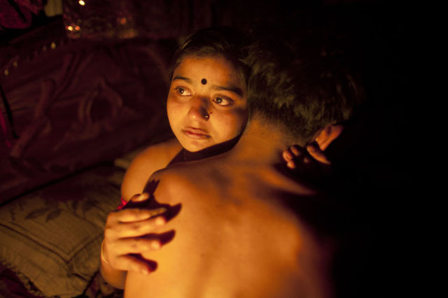 """ATTENTION EDITORS: THIS PICTURE IS 1 OF 25 TO ACCOMPANY PICTURE PACKAGE 'BANGLADESH - TEENAGE PROSTITUTES'. SEARCH FOR KEYWORD """"BROTHEL"""" TO SEE ALL IMAGES PXP101-125. Seventeen-year-old prostitute Hashi, embraces a Babu, her """"husband"""", inside her small room at Kandapara brothel in Tangail, a northeastern city of Bangladesh, March 4, 2012. Many young and inexperienced prostitutes have """"lovers"""" or """"husbands"""" who normally live outside the brothel occasionally taking money and sex from them in exchange for security in this male dominated society. She earns about 800-1000 taka daily ($9.75 - $12.19) servicing around 15-20 customers every day. Hashi is one of hundreds of mostly teenage sex workers living in a painful life of exploitation in Kandapara slum's brothel who take Oradexon, a steroid used by farmers to fatten their cattle, in order to gain weight and appear """"healthier"""" and more attractive to clients. Picture taken March 4, 2012. REUTERS/Andrew Biraj (BANGLADESH - Tags: SOCIETY BUSINESS EMPLOYMENT HEALTH DRUGS TPX IMAGES OF THE DAY)"""